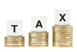 Taxation, accounting and finance concept. The word TAX on lettered dice on a row of gold coin stacks. Isolated on a white background.