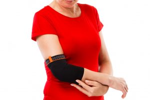 Tennis elbow - woman holding painful elbow isolated on white bac