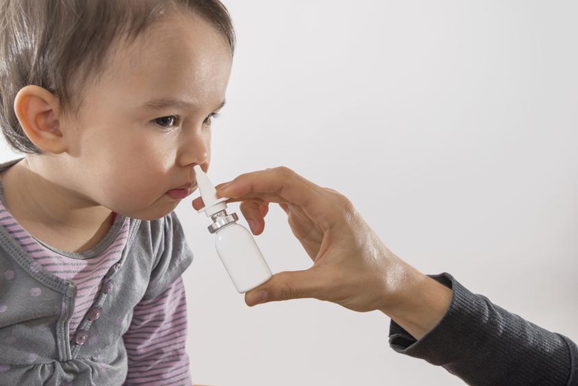 parent's hand of a girl applies a nasal spray