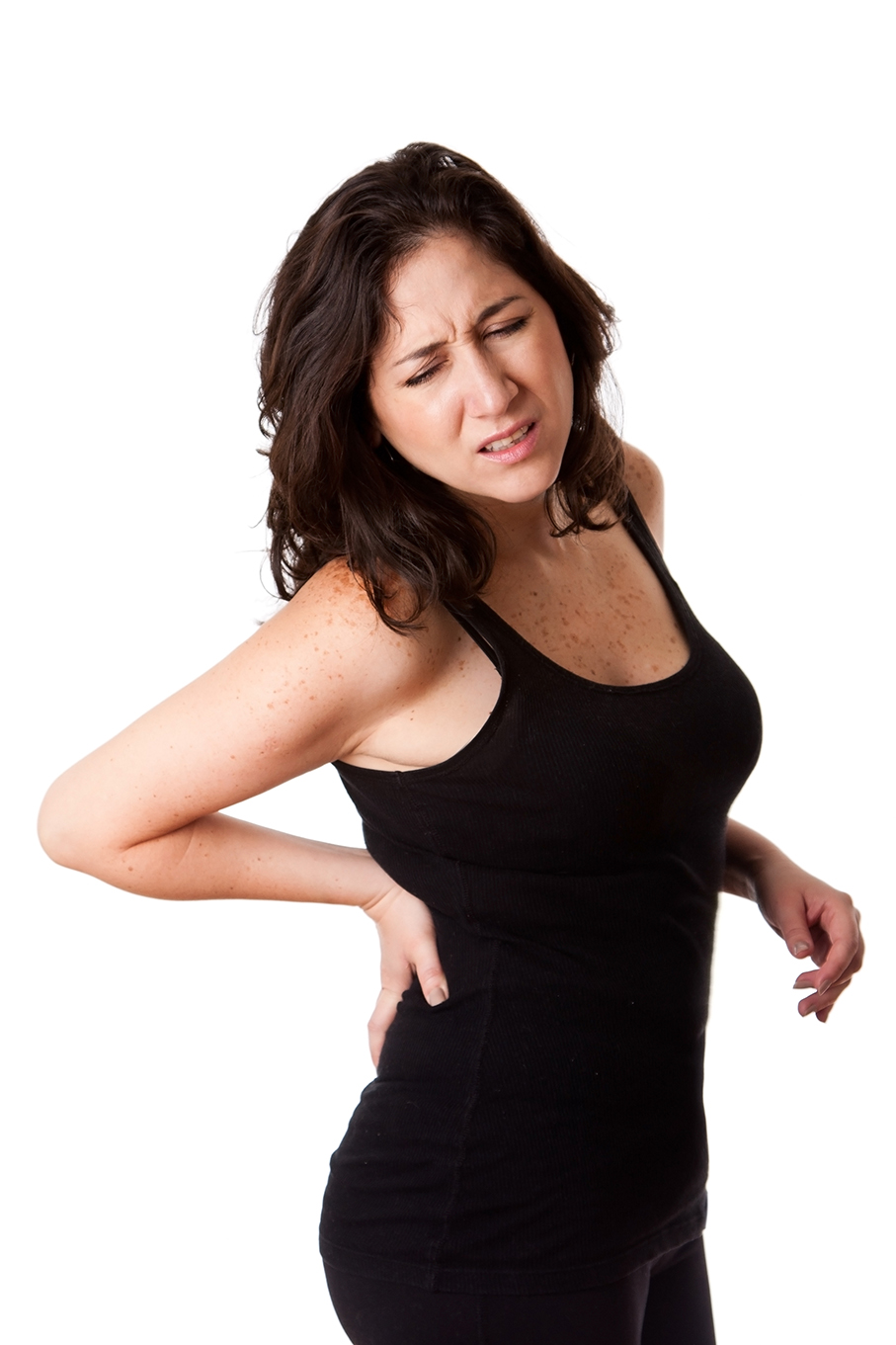 Beautiful woman holding her back with pain and ache due to injury,wearing a sporty black tank top, isolated.